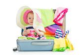 Niña sentada en una maleta con las cosas para viajar de vacaciones — Foto de Stock