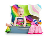 Baby girl sitting in suitcase with things for vacation travel — Stok fotoğraf