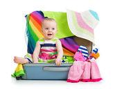 Kleines mädchen sitzt im koffer mit dingen für urlaubsreisen — Stockfoto