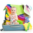 Baby girl sitting in suitcase with things for vacation travel — Stock Photo #26343761