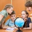 Royalty-Free Stock Photo: Pupils studying a globe together with teacher