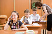 Primary school pupil using cell phone at lesson — Stok fotoğraf