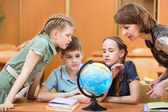 Pupils studying a globe together with teacher — Stock Photo