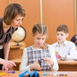 Schoolkids work at labour lesson. Teacher looking at pupil. — Stock Photo