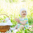 Baby eating apples from basket outdoors — Stock Photo