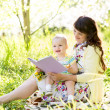 Stock Photo: Happy mother reading book to baby outdoors