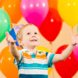 Stock Photo: Smiling child boy with balloons on birthday party