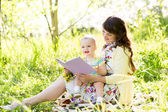 Happy mother reading a book to baby outdoors — Stock Photo
