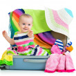 Baby girl sitting in suitcase with things for vacation travel — Stock Photo #27076083
