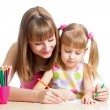 Stock Photo: Mother and her daughter pencil together