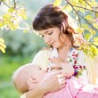 Young mother breast feeding her baby girl at sunny day — Stock Photo