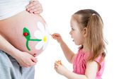Cute kid girl painting mother's belly — Stock Photo
