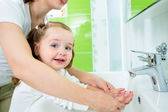 Mother washing baby hands — Stock Photo