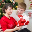 Young couple with gift in front of Christmas tree at home — Stock Photo