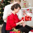 Young couple with gift in front of Christmas tree at home — 图库照片