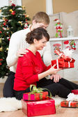 Young couple with gift in front of Christmas tree at home — Photo