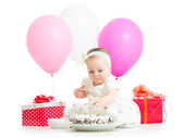 Baby girl touching light on birthday cake — Stock Photo