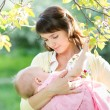 Young mother breast feeding her baby girl in garden — Stock Photo