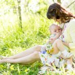 Young mother breast feeding her baby outdoors summertime — Stock Photo #28630773