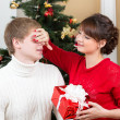 Happy woman closing man eyes by her hands with gift — Stock Photo