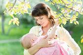 Junge mutter stillen ihr babymädchen im garten — Stockfoto