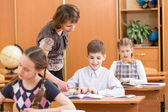 Schoolkids work at lesson. Teacher controling learning process. — Foto Stock
