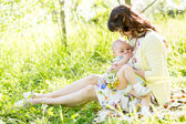 Young mother breast feeding her baby outdoors summertime — Stock Photo
