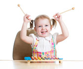 Cheerful child girl playing with musical toy — Stock Photo