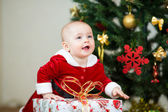 Kid girl dressed as Santa Claus in front of Christmas tree with — 图库照片