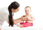 Doctor examining baby girl isolated on white background — Stock Photo