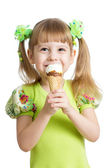 Happy child girl eating ice cream in studio isolated — Stock Photo