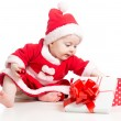Photo: SantClaus baby girl opening gift box isolated on white backgro