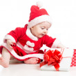 Stock Photo: SantClaus baby girl opening gift box isolated on white backgro