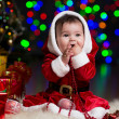 Kid girl dressed as Santa Claus near Christmas tree with gifts — Stock Photo