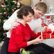 Young couple with gifts in front of Christmas tree  at home — Stok fotoğraf