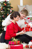 Young couple with gifts in front of Christmas tree at home — Stockfoto