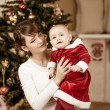 Mother and baby in front of Christmas tree at home — Stockfoto