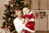 Mother and baby in front of Christmas tree at home — Stock Photo