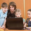 School kids and teacher using laptop at lesson — Stock Photo