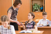 Teacher confiscating child's mobile phone at lesson in school — Stock Photo