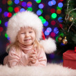 Funny baby in Santa Claus hat on bright festive background — Foto Stock