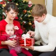 Young family at Christmas tree at home — Stock Photo #31892687