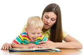 Happy mother reading a book to kid boy — Stockfoto