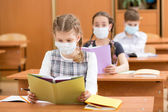 School kids with protection mask against flu virus at lesson — Stock Photo