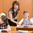 Stock Photo: School kids work at lesson. Teacher controlling learning process