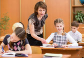 School kids work at lesson. Teacher controlling learning process — Foto Stock
