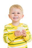 Kid boy drinking yoghurt from glass — Stock Photo