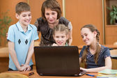 Schoolchildren and teacher using laptop at lesson — Stock Photo