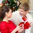 Young couple with gifts in front of Christmas tree at home — ストック写真
