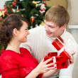 Young couple with gifts in front of Christmas tree at home — Stock Photo